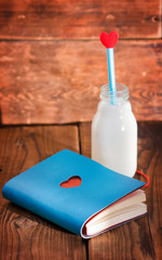 Notebook and bottle of milk with heart