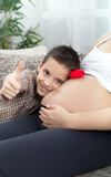 boy hugging belly of pregnant mother on sofa