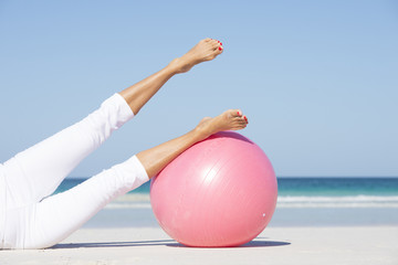 Woman stretching legs exercises at beach