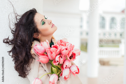 Beautiful young brunette woman with pink tulips in her hand