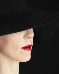Mujer con pamela negra y labios rojos.