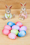 Funny rabbits ceramic with Easter eggs decorated with daisies