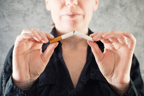 Woman quits smoking and breaking cigarette in half