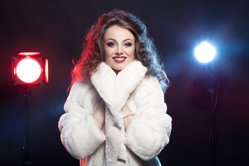 Woman in winter fur with two lights behind
