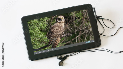 Tablet computer with headphones  on white background