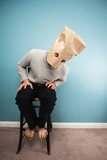 Man with bag over head on chair