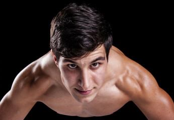 Muscle young man against dark background