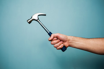 Man's hand holding hammer