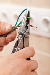 Electrician hands with pliers and wires