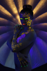 Sensual nude girl with fluorescent pattern on body