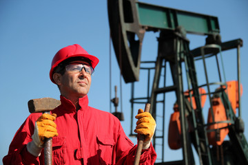Oil Industry Worker Holding Sledgehammer Next to Pump Jack.
