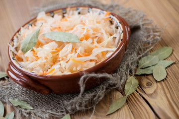 Ceramic bowl with sauerkraut over wooden background