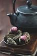 Green tea balls and asian cast-iron teapot, vertical shot