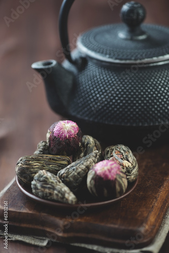 Green tea balls and asian cast-iron teapot, vertical shot