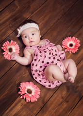 Sweet little baby girl crawling on a wooden floor