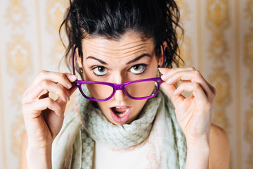Surprised woman looking over glasses