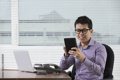 Asian businessman using a digital touchpad at work.