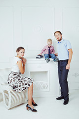 mother and father with little son on a white background