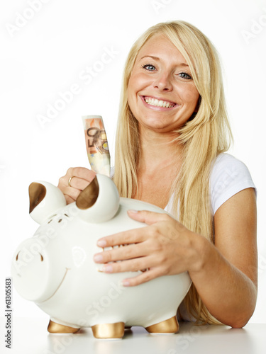 Pretty girl puts euro notes in her piggy bank