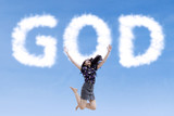 Religious woman jumping with clouds god