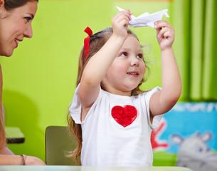 Frau mit Mädchen bastelt Origami