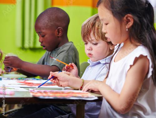 Kinder malen zusammen Bilder im Kindergarten