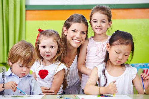 Erzieher und Kinder im Kindergarten malen