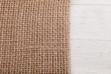Burlap or hessian on white wooden boards