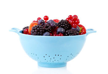 Blue colander with healthy fresh fruit over white background