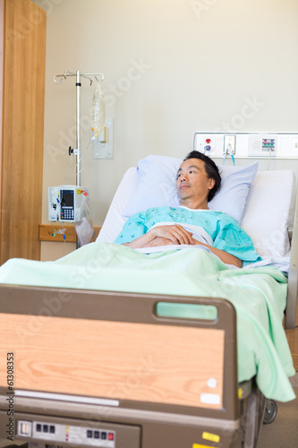 Thoughtful Patient Lying On Bed In Hospital