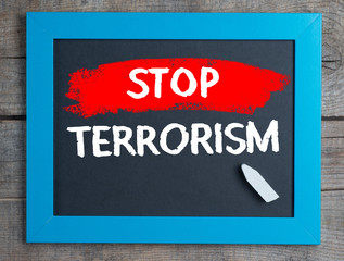 Stop Terrorism on blackboard on wooden table