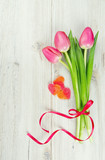 three pink tulips tied with a ribbon and valentine candy