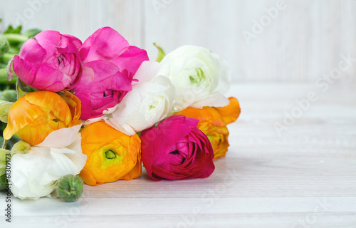 bouquet of white, pink and orange buttercups on wooden table