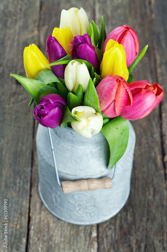 tulips in a milk can on wooden surface