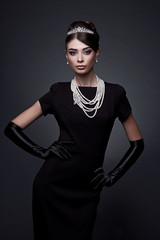 high fashion portrait of elegant woman in black dress and gloves