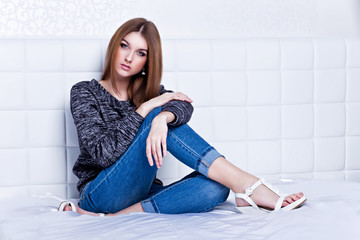 beautiful woman in jeans and sweater sitting on bed.