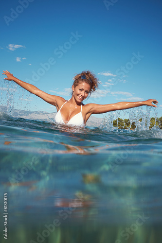 Happy young woman in sea with open hands.