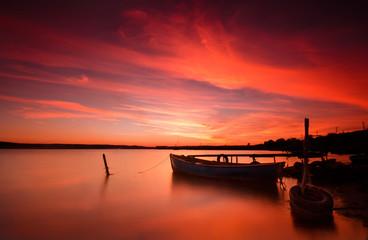 Оld fishing boat on the lake at sunset