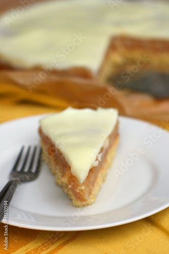 Piece of apple pie with vanilla icing on a white plate