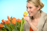 Woman smelling one yellow tulip spring flowers