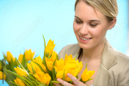 Woman looking down at spring yellow tulips