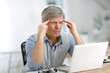 Senior businessman in front of laptop having a headache