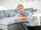 Mature man relaxing at home sitting on carpet