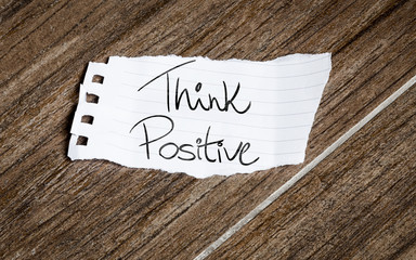 Think Positive written on the paper on a wood background