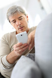 Attractive man sending text message on smartphone