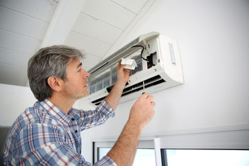 Repairman fixing air conditioner unit
