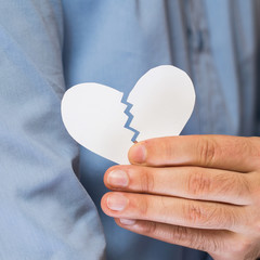 Hand with broken paper heart