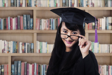 Graduated woman in library