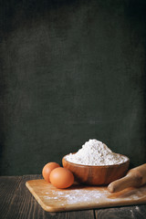 Flour and eggs on a blackboard background. copy space
