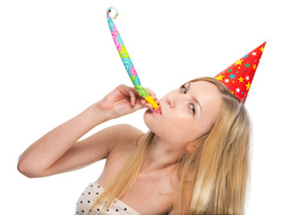 Young woman blowing into party horn blower